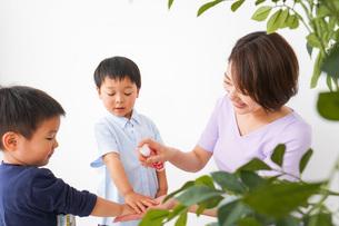 除菌スプレーを子どもにかけるお母さんの写真素材 [FYI04719820]
