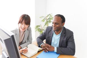 オフィスでパソコンを使う2人のビジネスパーソンの写真素材 [FYI04719897]