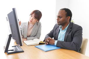 オフィスでパソコンを使う2人のビジネスパーソンの写真素材 [FYI04719899]