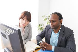 オフィスでパソコンを使う2人のビジネスパーソンの写真素材 [FYI04719900]