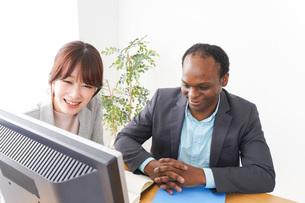 オフィスでパソコンを使う2人のビジネスパーソンの写真素材 [FYI04719903]