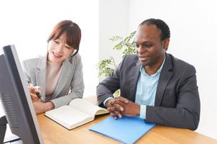 オフィスでパソコンを使う2人のビジネスパーソンの写真素材 [FYI04719905]