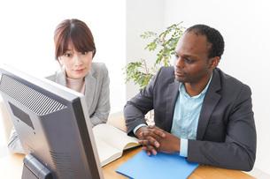 オフィスでパソコンを使う2人のビジネスパーソンの写真素材 [FYI04719906]