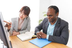 オフィスでパソコンを使う2人のビジネスパーソンの写真素材 [FYI04719907]