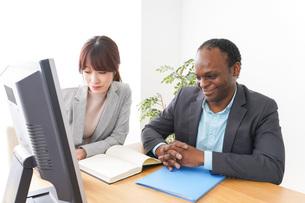 オフィスでパソコンを使う2人のビジネスパーソンの写真素材 [FYI04719909]