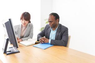 オフィスでパソコンを使う2人のビジネスパーソンの写真素材 [FYI04719910]