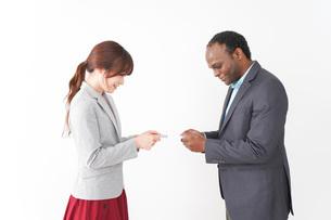 名刺交換をする2人のビジネスパーソンの写真素材 [FYI04719925]