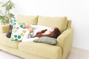 部屋でリラックスをする若い女性の写真素材 [FYI04719975]