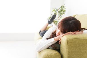 部屋でリラックスをする若い女性の写真素材 [FYI04719986]