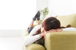 部屋でリラックスをする若い女性の写真素材 [FYI04719988]