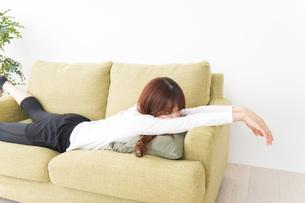 部屋でリラックスをする若い女性の写真素材 [FYI04719990]