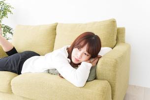 部屋でリラックスをする若い女性の写真素材 [FYI04719991]