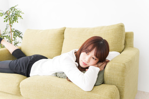 部屋でリラックスをする若い女性の写真素材 [FYI04719992]
