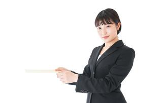 書類を提出するスーツを着たビジネスウーマンの写真素材 [FYI04720136]