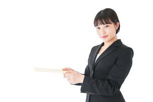 書類を提出するスーツを着たビジネスウーマンの写真素材 [FYI04720140]