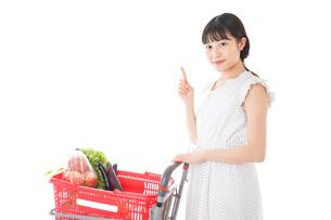 スーパーでポイントを指差す若い女性の写真素材 [FYI04720291]