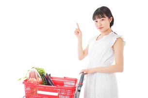 スーパーでポイントを指差す若い女性の写真素材 [FYI04720294]