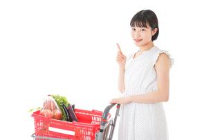 スーパーでポイントを指差す若い女性の写真素材 [FYI04720295]