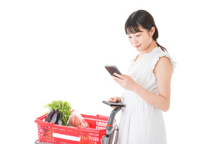 スーパーで食料品を調べる若い女性の写真素材 [FYI04720316]