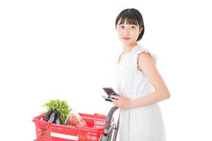 スーパーで食料品を調べる若い女性の写真素材 [FYI04720319]