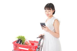 スーパーで食料品を調べる若い女性の写真素材 [FYI04720322]