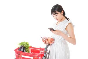 スーパーで食料品を調べる若い女性の写真素材 [FYI04720326]