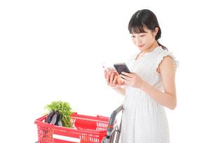 スーパーで食料品を調べる若い女性の写真素材 [FYI04720328]