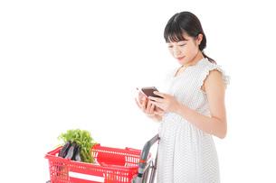 スーパーで食料品を調べる若い女性の写真素材 [FYI04720329]