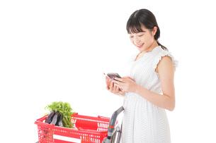 スーパーで食料品を調べる若い女性の写真素材 [FYI04720331]