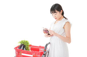スーパーで食料品を調べる若い女性の写真素材 [FYI04720332]