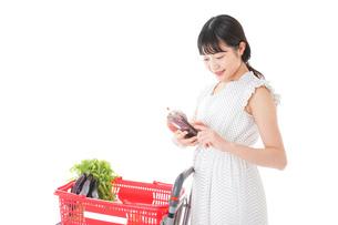 スーパーで食料品を調べる若い女性の写真素材 [FYI04720334]