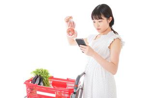 スーパーで食料品を調べる若い女性の写真素材 [FYI04720335]