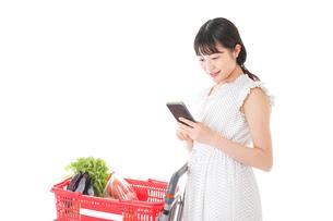 スーパーで食料品を調べる若い女性の写真素材 [FYI04720342]