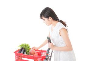 スーパーで食料品を調べる若い女性の写真素材 [FYI04720343]