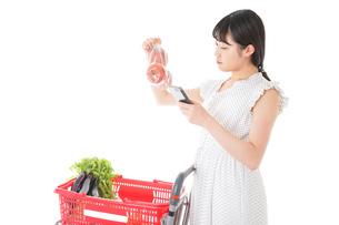 スーパーで食料品を調べる若い女性の写真素材 [FYI04720344]