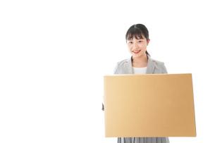 荷物を運ぶ若いビジネスウーマンの写真素材 [FYI04720485]