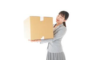 荷物を運ぶ若いビジネスウーマンの写真素材 [FYI04720487]