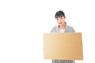 荷物を運ぶ若いビジネスウーマンの写真素材 [FYI04720491]