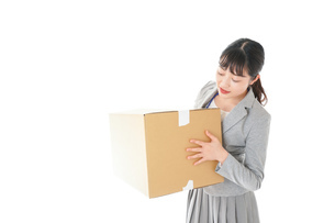 荷物を運ぶ若いビジネスウーマンの写真素材 [FYI04720493]