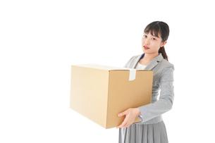 荷物を運ぶ若いビジネスウーマンの写真素材 [FYI04720497]