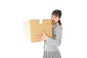 荷物を運ぶ若いビジネスウーマンの写真素材 [FYI04720499]