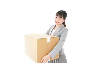 荷物を運ぶ若いビジネスウーマンの写真素材 [FYI04720501]