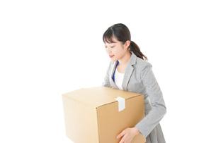 荷物を運ぶ若いビジネスウーマンの写真素材 [FYI04720502]