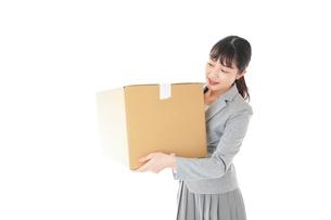 荷物を運ぶ若いビジネスウーマンの写真素材 [FYI04720503]