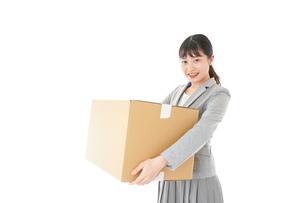 荷物を運ぶ若いビジネスウーマンの写真素材 [FYI04720504]