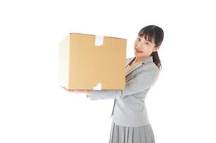 荷物を運ぶ若いビジネスウーマンの写真素材 [FYI04720505]