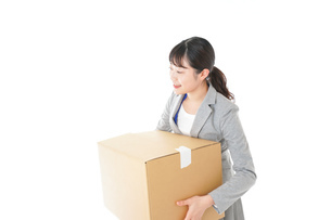 荷物を運ぶ若いビジネスウーマンの写真素材 [FYI04720506]