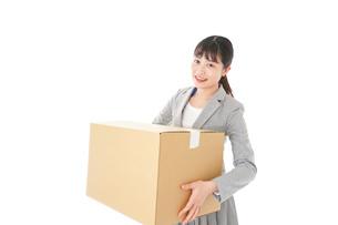 荷物を運ぶ若いビジネスウーマンの写真素材 [FYI04720508]