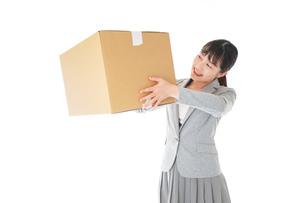 荷物を運ぶ若いビジネスウーマンの写真素材 [FYI04720509]