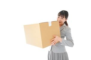 荷物を運ぶ若いビジネスウーマンの写真素材 [FYI04720510]